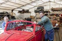Smiling mechanics pushing boy in classic car in auto repair shop — Photo de stock
