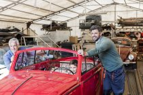 Smiling mechanics pushing boy in classic car in auto repair shop — Stock Photo