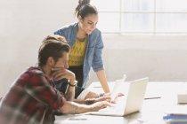 Kreative junge Geschäftsleute am Laptop im sonnigen Büro — Stockfoto