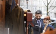 Couple window shopping outside menswear shop — Stock Photo