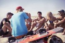 Friends learning kiteboarding on sunny beach — Stock Photo