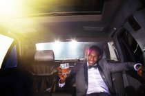 Celebrity drinking cocktail inside limousine outside event — Stock Photo