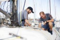 Zwei kaukasische junge Männer bereiten Segelboot vor — Stockfoto
