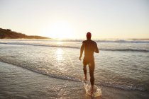 Male triathlete swimmer in wet suit running into ocean surf at sunrise — Stock Photo