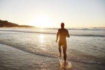 Männliche Triathlet Schwimmer im Neoprenanzug läuft in Meeresbrandung bei Sonnenaufgang — Stockfoto