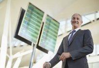 Portrait smiling businessman standing below arrival departure board in airport — Stock Photo