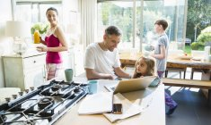 Family with breakfast and laptop in morning kitchen — Stock Photo