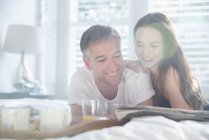 Smiling couple reading newspaper in sunny bedroom — Stock Photo