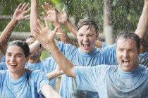 Equipo entusiasta animando bajo la lluvia en el campamento de entrenamiento - foto de stock