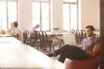 Lächelnde lässige Geschäftsmann tragen von Kopfhörern und arbeiten am Laptop auf bohnenbeutelstuhl im Büro — Stockfoto