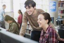 Étudiants utilisant un ordinateur dans une salle de classe informatique — Photo de stock