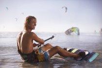 Smiling man ready to kiteboard on beach — Stock Photo