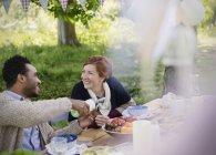 Lächelnde paar gießt Wein an Gartenparty Tisch — Stockfoto