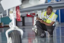 Ground crew worker with clipboard checking airplane — Stock Photo