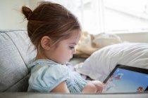 Chica usando tableta digital en el sofá - foto de stock