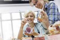 Smiling mature women painting pottery in studio — Stockfoto