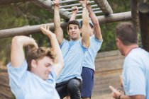 Determined man swinging on monkey bars on boot camp obstacle course — Stock Photo