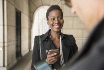 Empresário e empresária com telefones celulares — Fotografia de Stock