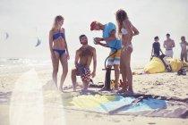 Друзья готовят кайтбординг на солнечном пляже — стоковое фото
