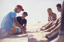Friends talking drawing line in sand on sunny beach — Stock Photo