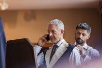 Кравець припасування бізнесмен стільниковий телефон для масті в магазин чоловічого одягу — стокове фото