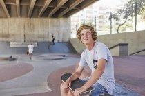 Portrait smiling teenage boy with skateboard at skate park — Stock Photo