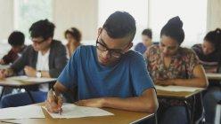 Masculino universitário fazendo prova na mesa na sala de aula — Fotografia de Stock