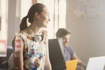 Усміхаючись бізнес-леді з навушниками в сучасні офісні — стокове фото