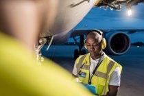 Экипаж наземного управления воздушным движением работает под самолетом на взлетной полосе аэропорта — стоковое фото