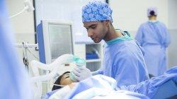 Anesthésiste tenant un masque à oxygène sur le visage des patients en salle d'opération — Photo de stock