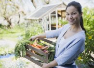 Portrait smiling woman with fresh harvested crate of vegetables in garden — Stock Photo