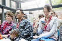 Женщина смс с мобильного телефона в аудитории на технологической конференции — стоковое фото