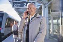 Smiling businessman talking on cell phone outside airport — Stock Photo