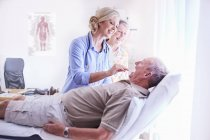Доктор, изучения старший мужчина рот на осмотр — стоковое фото
