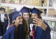 Female college graduates in cap and gown taking selfie — Stock Photo