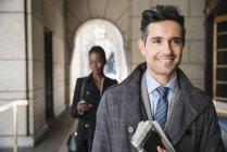 Empresário corporativo sorridente carregando jornal e celular no claustro — Fotografia de Stock