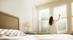 Frau im Bademantel öffnet Schlafzimmerfenster — Stockfoto