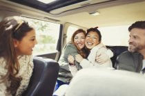 Enthusiastic female friends hugging in back seat of car — Stock Photo