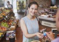 Mujer pagando con tarjeta de crédito en caja de supermercado - foto de stock