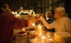 Friends toasting champagne glasses at candlelight Christmas dinner party — Stock Photo