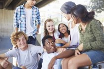 Teenage friends hanging out talking at skate park — Stock Photo