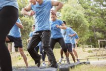 Déterminée gens sautant des pneus sur la course d'obstacles de boot camp — Photo de stock