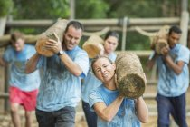 Determined people running with logs on boot camp obstacle course — Stock Photo