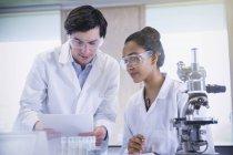 Étudiants menant une expérience scientifique au microscope dans une salle de classe de laboratoire de sciences — Photo de stock