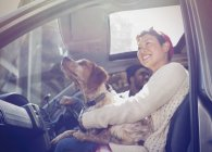 Smiling woman holding dog on lap in car — Stock Photo