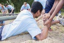 Товариш по команді, допомагаючи людині на boot camp, звичайно — стокове фото