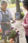 Woman with flowers watching plant nursery worker using credit card machine — Stock Photo