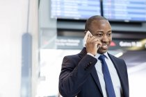 Businessman talking on cell phone in airport — Stock Photo