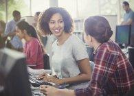 Étudiantes utilisant des ordinateurs dans une bibliothèque de laboratoire informatique — Photo de stock