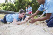 Партнер по команде помогает целеустремленной женщине ползти по полосе препятствий учебного лагеря — стоковое фото